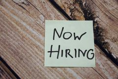 Now Hiring written on an yellow sticky note paper on the wooden background. Now Hiring written on an yellow sticky note paper on the wooden oak background Stock Photo