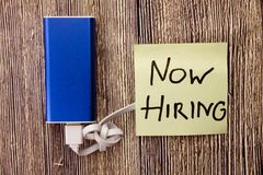 Now Hiring written on yellow sticky note pinned with blue push pin on cork bulletin board. Now Hiring written on an yellow sticky note pinned with blue push pin Stock Image