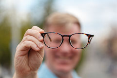 Now I can see you well. Handsome young man holding glasses and looking through them Stock Images