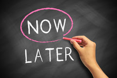 Now or Later. Choosing Now instead of Later, selected with red chalk on blackboard Royalty Free Stock Photo