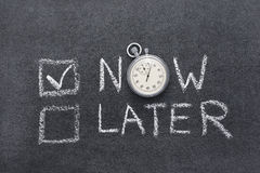 Now or later. Concept handwritten on chalkboard with vintage precise stopwatch used instead of O Royalty Free Stock Photos
