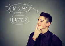 Now or later. Man thinking making up his mind Stock Image
