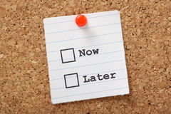 Now or Later?. Now or Later tick boxes on a paper note pinned to a cork notice board Stock Photography
