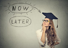 Now or later. Woman student thinking looking up royalty free stock photo