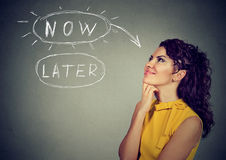 Now or later. Woman thinking looking up Stock Images