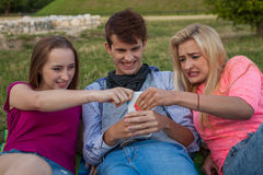 Now my turn! Three friends  fighting for a mobile phone. Royalty Free Stock Photo