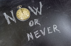 Now or Never. Concept on chalk table whit an old pocket watch royalty free stock image
