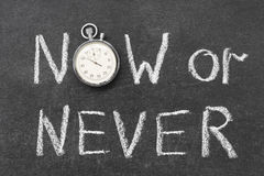 Now or never. Concept handwritten on chalkboard with vintage precise stopwatch used instead of O Royalty Free Stock Image