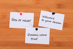 Now or never! Welcome to your dream. Dreams come true! Note pin on the bulletin board. Now or never! Welcome to your dream. Dreams come true! Note pin on the royalty free stock photo