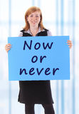 Now or never. Young beauty business woman hold paper with now or never text Stock Photo