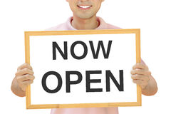 NOW OPEN sign on whiteboard held by smiling man Royalty Free Stock Image