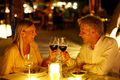 Now that is romantic. Mature couple enjoying candlelight dinner in a restaurant toasting wine glasses Stock Photography
