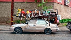 Now that`s a handyman, a dude who put a lumber rack on his little sedan and strapped all his tools and equipment to it. Royalty Free Stock Image