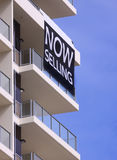 Now Selling sign. Now Selling banner hangs from the balcony of a high rise apartment block Stock Image
