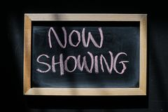 Now showing - words on black board. Now showing - words hand written with chalk on blackboard royalty free stock photography