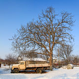 Now unused truck in snow. These trucks can be seen in many Bulgarian villages - abandoned to rust under a tree Royalty Free Stock Images