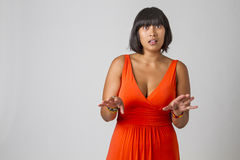 Now wait a second. Young asian woman with low cut orange dress, holding her hand up trying to explain something royalty free stock images