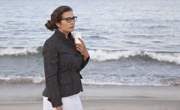 Now What?. Woman with cup of coffee at the beach Royalty Free Stock Photo