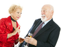 Now You Behave. Senior couple at a party.  The husband is drunk and the wife is angry at him.  Isolated on white Royalty Free Stock Image