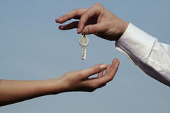 Now you have the solution. Hand giving a key and one receiving it Royalty Free Stock Photo