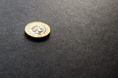 Nowa brytyjska jeden niezawodna funtowa moneta na ciemnym tle Fotografia Stock