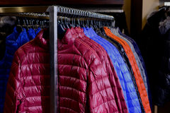 Nowa kolekcja puszek kurtki na wieszakach w rynku z bliska Obraz Stock