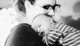 Nowa matka Trzyma Nowonarodzonej chłopiec Zawija w koc Gdy Śpi na jej klatki piersiowej Czarnej & Białej fotografii zdjęcie stock