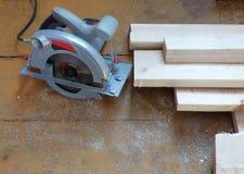Nowe świeże deski i elektryczna kurenda zobaczyli na starzejącym się drewnianym nawierzchniowym stole lub podłoga tło abstrakcjon obrazy stock