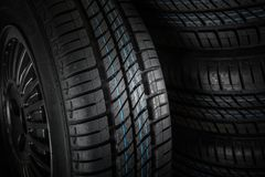 Nowe i nieużywane samochodowe opony przeciw ciemnemu tłu Zdjęcia Stock
