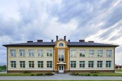 Nowego nowożytnego jednopiętrowego dziecina preschool budynek z dużymi okno na zielonej trawiastej gazonu i niebieskiego nieba ko obraz stock