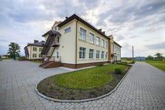 Nowego nowożytnego jednopiętrowego dziecina preschool budynek z dużymi okno na zielonej trawiastej gazonu i niebieskiego nieba ko obraz royalty free