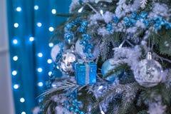 Nowego Roku drzewo dekorował z błękitnymi zabawkami - prezenty i piłki zamazuje Błękitnego bokeh tło dla festiwalu świętowania bo Fotografia Stock