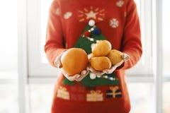 Nowego roku i zimy pojęcie Cropped strzał kobieta w śmiesznej boże narodzenie puloweru mienia pomarańcze i tangerines, ofiara fotografia royalty free