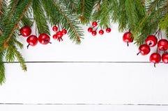Nowego Roku ` s, Bożenarodzeniowy temat Zielone jedlinowe gałąź, dekoracyjne jagody na białym drewnianym tle Zdjęcia Royalty Free