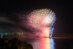 Nowego Roku ` s wigilii fajerwerki wszczynający od wody z odbiciami Fotografia Stock