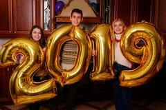 Nowi 2019 rok przychodzi Grupa rozochoceni młodzi ludzie nieść zdjęcia royalty free
