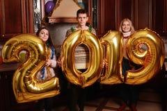 Nowi 2019 rok przychodzi Grupa rozochoceni młodzi ludzie nieść zdjęcie royalty free