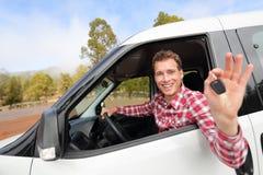 Nowi samochody - mężczyzna napędowy samochodowy pokazuje samochód wpisuje szczęśliwego obraz royalty free