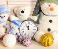 Nowmen, osos de peluche y bolas del árbol de navidad cerca del despertador foto de archivo libre de regalías