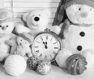 Nowmen, osos de peluche y bolas del árbol de navidad cerca del despertador imagenes de archivo