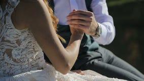 Nowożeniec trzyma panny młodej rękę, delikatnie pieści ona Zakończenie zbiory wideo