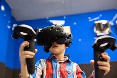 Nowożytna technologia, hazard i ludzie pojęć, - chłopiec w rzeczywistości wirtualnej słuchawki lub 3d szkłach bawić się gra wideo zdjęcie royalty free