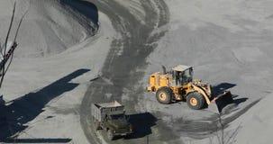 Nowożytny buldożer pracuje w karierze, buldożeru ładunków pomarańczowi kamienie w usyp ciężarówkę zbiory