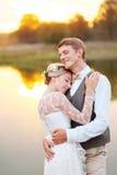 Nowożeńcy ściskają each inny na jeziorze przy zmierzchem Jezioro odbija drzewa i niebo Fotografia Stock