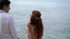 Nowożeńcy chodzi na plażowym pobliskim morzu przy zmierzchem lub wieczór Trzymać ręki, ściska Romantyczny pobliski ocean zdjęcie wideo