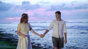 Nowożeńcy chodzi na plażowym pobliskim morzu przy zmierzchem lub wieczór Trzymać ręki, ściska Romantyczny pobliski ocean zbiory