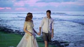 Nowożeńcy chodzi na plażowym pobliskim morzu przy zmierzchem lub wieczór Trzymać ręki, ściska Romantyczny pobliski ocean zbiory wideo