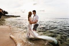 Nowożeńcy na plaży przy zmierzchem obraz stock