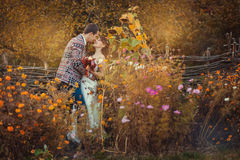 Nowożeńcy obejmują wśród kwiatów Obraz Stock
