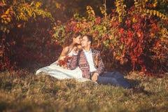 Nowożeńcy obejmuje siedzieć na trawie blisko drzewa obrazy royalty free